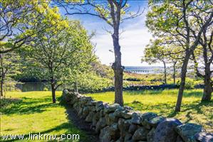 Looking across ancient stone walls and green fields to the water beyond.