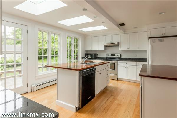 Newly renovated bright kitchen with access to spacious side yard and deck.
