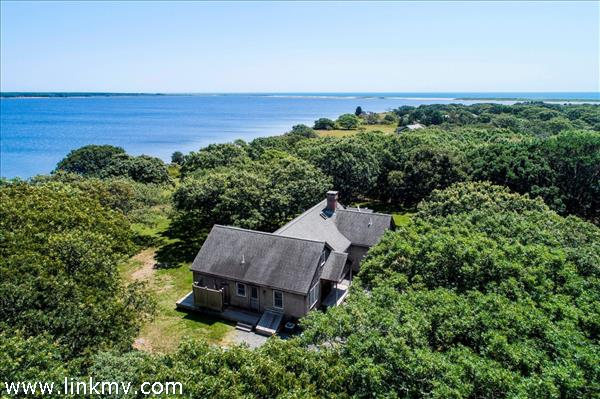 The house looks out over miles of open blue water, with views of Tisbury Great Pond and the Atlantic.