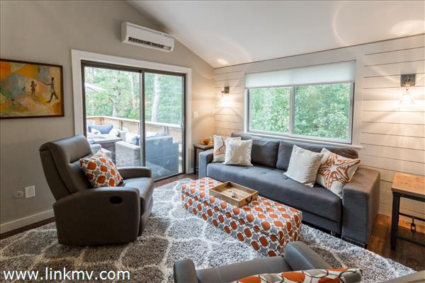 Spacious living room with slider to deck beyond.