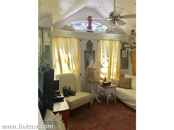 Living room w/antique eyebrow window, cathedral bead-board ceilings, ceiling fan and hardwood floors,