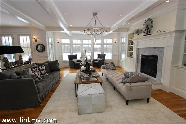 Living room with fireplace looking out to back yard and pool.