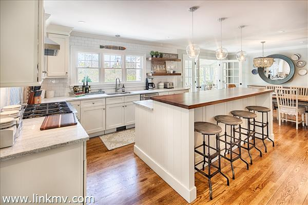 Spacious kitchen with granite counters, stainless appliances, and two level center island breakfast bar.