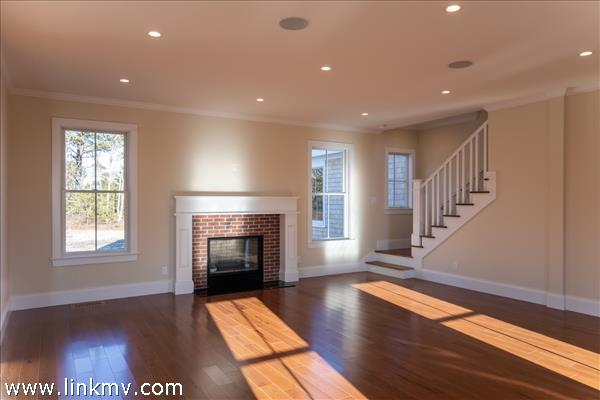 Living with gas fireplace and stairway to second level