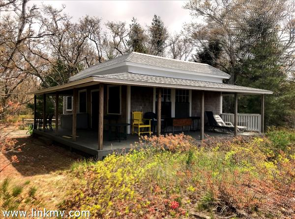 Sweet cottage surrounded by the wraparound porch