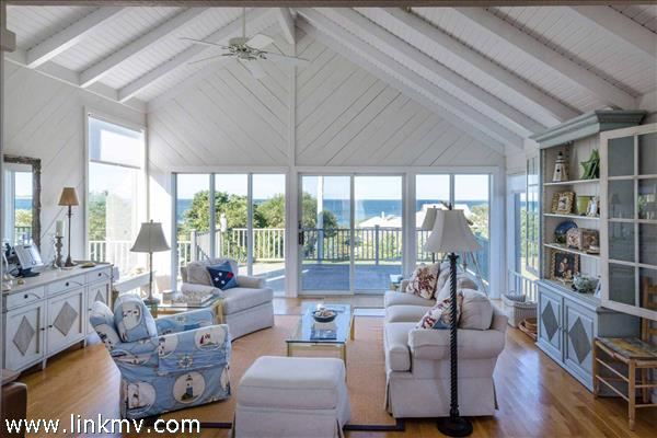 Living Room Has Vaulted Ceilings and Glass Doors Leading Out to Large Wrap Around Deck with Ocean Views