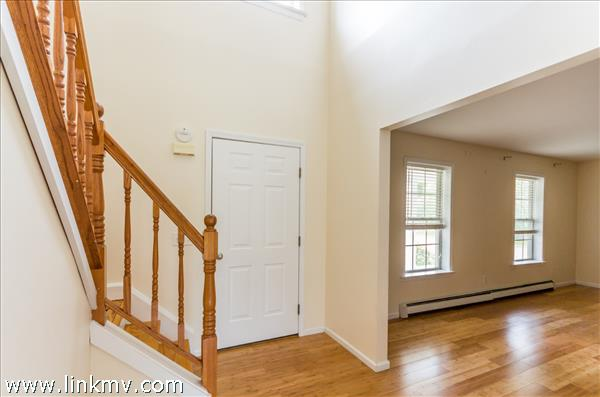 Front entry is warm and inviting, looking into living room.