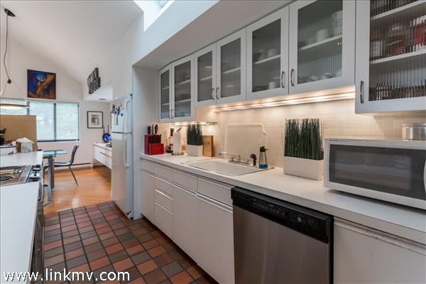 The kitchen is cleverly located nearby yet tucked away for privacy.