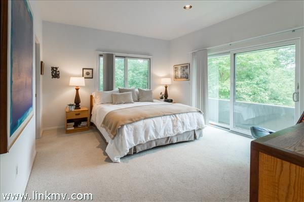 Bright master bedroom with sliders to private deck...
