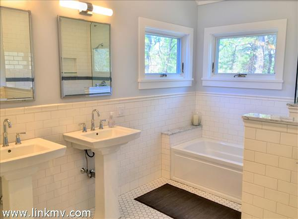 Renovated master bathroom with subway tile, carrara marble trim and cathedral ceiling