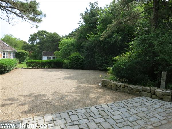 Plenty of parking in pea stone driveway with stone wall.