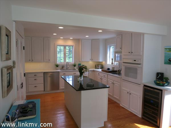 Kitchen with carrera marble counters and built in oven and wine fridge. 14 X 15
